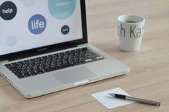 Ordenador, taza de café con las letras, pluma y papel para las notas imagen de archivo