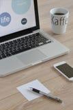 Ordenador, teléfono móvil, taza de café con las letras, pluma y papel para las notas fotos de archivo libres de regalías