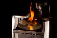 Ordenador y Cd en el fuego Imagen de archivo libre de regalías