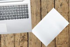 Ordenador y documento sobre la tabla de madera Imagen de archivo libre de regalías