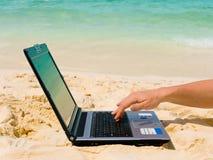 Ordenador y mano en la playa Imagen de archivo libre de regalías