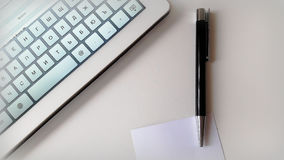 Ordenador y pluma en la tabla Imagenes de archivo