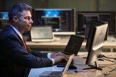 Ordenadores de Working On Multiple del hombre de negocios imagenes de archivo