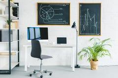 Ordenadores en la tabla en oficina ligera con las cartas de negocio fotografía de archivo