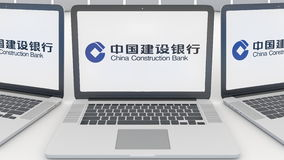 Ordenadores portátiles con el logotipo de China Construction Bank en la pantalla Representación conceptual del editorial 3D de la Imagen de archivo libre de regalías
