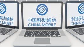 Ordenadores portátiles con el logotipo de China Mobile en la pantalla Representación conceptual del editorial 3D de la informátic Imagenes de archivo