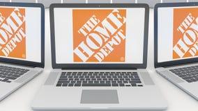 Ordenadores portátiles con el logotipo de Home Depot en la pantalla Representación conceptual del editorial 3D de la informática Fotografía de archivo libre de regalías