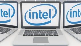 Ordenadores portátiles con el logotipo de Intel Corporation en la pantalla Representación conceptual del editorial 3D de la infor stock de ilustración