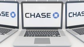 Ordenadores portátiles con el logotipo de JPMorgan Chase Bank en la pantalla Representación conceptual del editorial 3D de la inf Fotografía de archivo