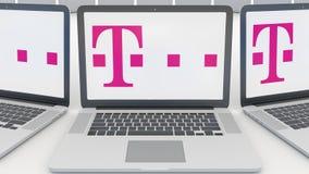 Ordenadores portátiles con el logotipo de T-Mobile en la pantalla Representación conceptual del editorial 3D de la informática Fotografía de archivo libre de regalías
