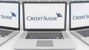 Ordenadores portátiles con el logotipo del grupo de Credit Suisse en la pantalla Representación conceptual del editorial 3D de la Imagen de archivo