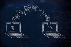 Ordenadores portátiles con los documentos que vuelan a partir de una pantalla a la otra Imagen de archivo