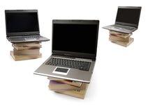 Ordenadores portátiles en pilas de libros Fotos de archivo