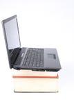 Ordenadores portátiles encendido densamente de libros Imagenes de archivo