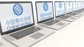 Ordenadores portátiles modernos con el logotipo de China Mobile Representación conceptual del editorial 3D de la informática Fotos de archivo