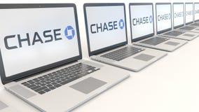 Ordenadores portátiles modernos con el logotipo de JPMorgan Chase Bank Representación conceptual del editorial 3D de la informáti Foto de archivo