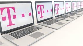 Ordenadores portátiles modernos con el logotipo de T-Mobile Representación conceptual del editorial 3D de la informática Foto de archivo libre de regalías