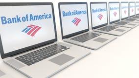 Ordenadores portátiles modernos con la Bank of America el logotipo Representación conceptual del editorial 3D de la informática Fotografía de archivo