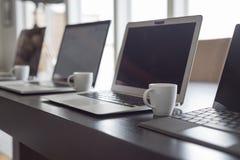 Ordenadores portátiles y café express alineados imágenes de archivo libres de regalías