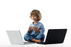 Ordenadores portátiles y smartphone del wiyh del niño pequeño imagen de archivo
