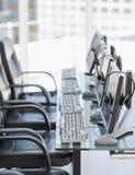 Ordenadores y auriculares de las sillas en oficina moderna fotografía de archivo