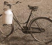 Ordenhando a bicicleta com o escaninho para o leite transporte o efeito do sepia Fotografia de Stock Royalty Free