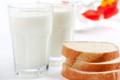 Ordenhe em um vidro e em partes do pão branco Fotografia de Stock