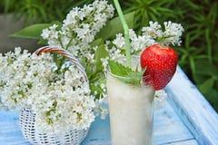 Ordenhe o batido com banana e morangos em um fundo do lilás do branco das flores Fotos de Stock
