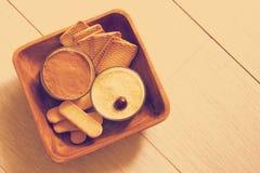 Ordenhe o bolo de queijo, decorado com cerejas, nos vidros com cookies em uma bacia de madeira em uma porcelana na manhã do iníci Fotografia de Stock Royalty Free