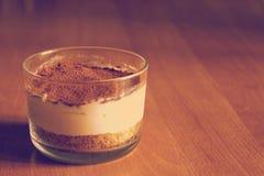 Ordenhe o bolo de queijo, decorado com migalhas do café, em uma tabela de madeira em um fundo borrado na manhã do início do verão Foto de Stock
