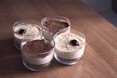 Ordenhe o bolo de queijo nos vidros, decorados com migalhas do café, cookies e cerejas, em uma tabela de madeira em um fundo borr Imagens de Stock