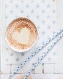 Ordenhe o chá com o coração feito da canela em um fundo de madeira branco Imagem de Stock