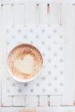 Ordenhe o chá com o coração feito da canela em um fundo de madeira branco Fotos de Stock