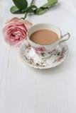 Ordenhe o chá em um copo e em uns pires da porcelana, com rosas cor-de-rosa Imagem de Stock Royalty Free