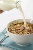 Ordenhe o derramamento na bacia de cereal Imagens de Stock Royalty Free