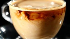 Ordenhe o derramamento no café em um vidro no movimento lento video estoque
