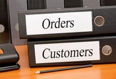 Ordens e clientes - duas pastas com texto no escritório fotografia de stock royalty free