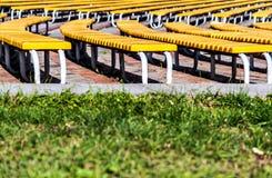 ordentliche Reihen von grünen Bänke auf einem Grashintergrund Stockfotografie