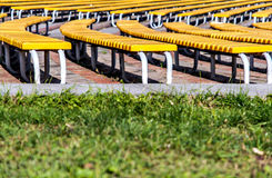 ordentliche Reihen von grünen Bänke auf einem Grashintergrund Lizenzfreie Stockbilder