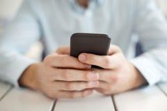 Ordentlicher Mann, der an einem modernen Telefon schreibt stockfoto