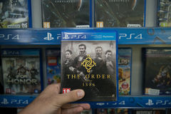 The Order 1886. Bratislava, Slovakia, circa april 2017: Man holding The Order 1886 videogame on Sony Playstation 4 console in store Royalty Free Stock Images