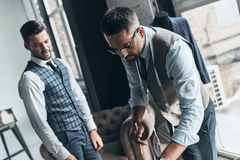 Order details. Two young fashionable men having a discussion while standing in workshop royalty free stock photography