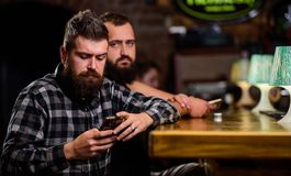 Order drinks at bar counter. Men with smartphone relaxing at bar. Mobile dependence concept. Mobile phone always with me. Friday relaxation in bar. Hipster royalty free stock photo