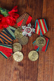 Order of the Patriotic War in St. and Medals for the victory over Germany and two red flower on a table. close up. selective focus Royalty Free Stock Photography