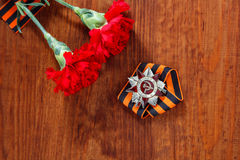 Order of the Patriotic War in St. and two red flower and George ribbon on wooden Royalty Free Stock Photos