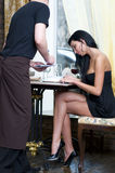 Order in restaurant. Beautiful woman in restaurant. Waiter is taking order Stock Images