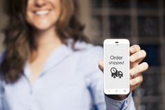 Order shipped message. Woman showing her mobile phone. Royalty Free Stock Image