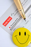Order and survey sheet. A golden pen putting on a order and survey sheet, with a smiling face, shown as successful and happy selling or business purchase, or Stock Photography