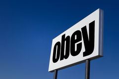 The order to obey. Big ad panel, embossed with the order to obey, isolated on blue sky royalty free stock photography