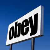 Order to OBEY. Horizontal billboard with the order to OBEY, against irreal blue sky. Abstract concept of consumerism, human mind control, power of corporations stock images